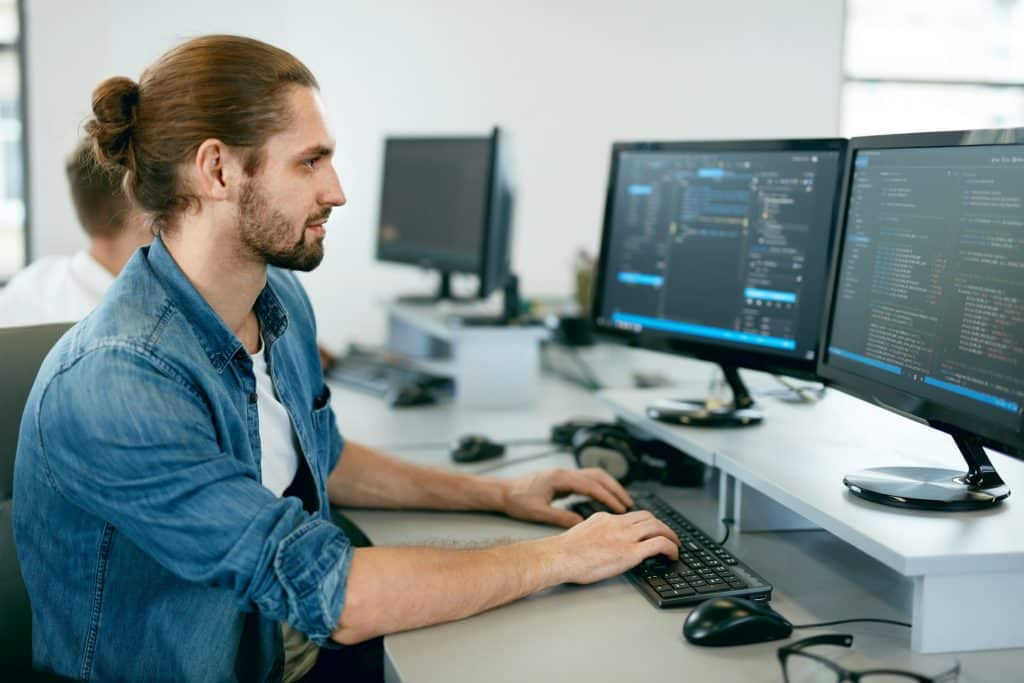 Programming.,Man,Working,On,Computer,In,It,Office,,Sitting,At